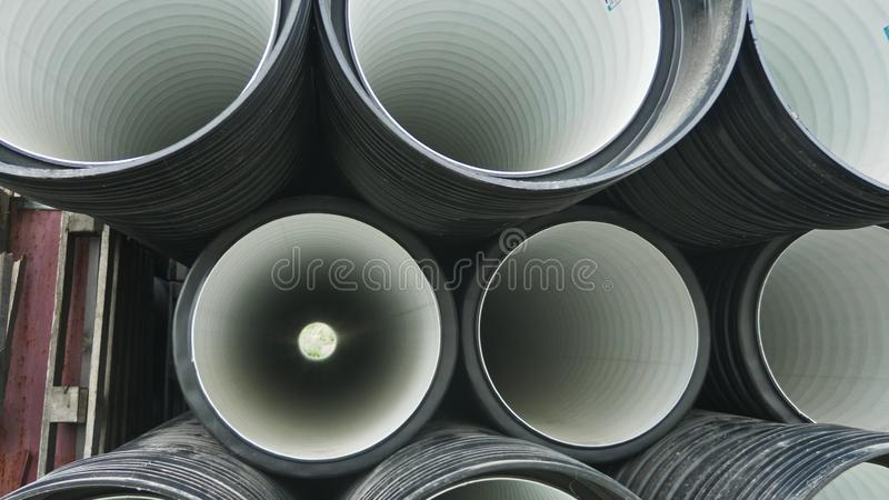 Warehouse of finished plastic pipes industrial outdoors storage site. Manufacture of plastic water pipes factory. royalty free stock photo