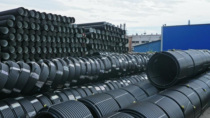 Warehouse of finished plastic pipes industrial outdoors storage site. Manufacture of plastic water pipes factory. stock photo