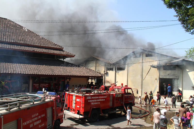 Warehouse on fire. Residents and the firemen tries to extinguish charmingly flaring up in a warehouse in solo, central java, indonesia royalty free stock photo