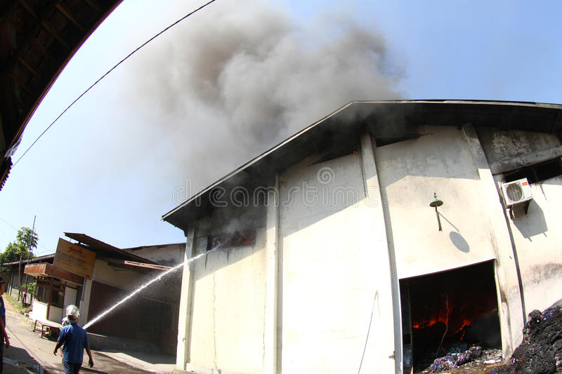 Warehouse on fire. Residents and the firemen tries to extinguish charmingly flaring up in a warehouse in solo, central java, indonesia royalty free stock photos