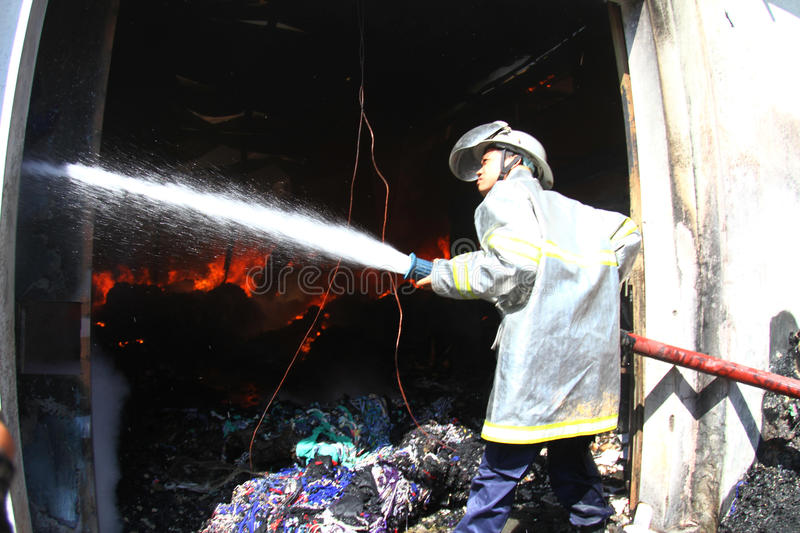 Warehouse on fire. Residents and the firemen tries to extinguish charmingly flaring up in a warehouse in solo, central java, indonesia stock photos