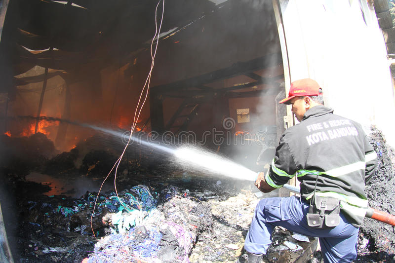 Warehouse on fire. Residents and the firemen tries to extinguish charmingly flaring up in a warehouse in solo, central java, indonesia royalty free stock image