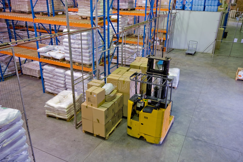 Warehouse forklift. Inside of commercial warehouse with goods stacked and forklift stock images