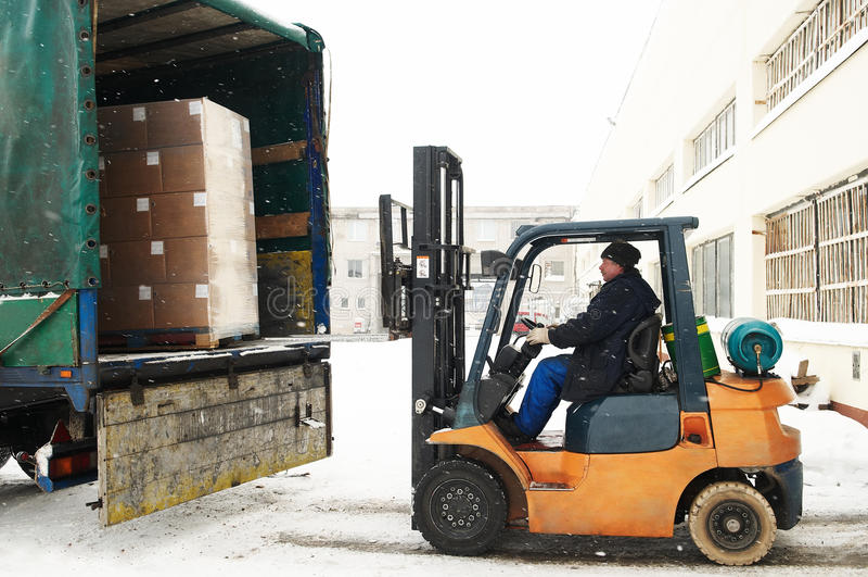 Warehouse forklift loader work. Warehouse forklift loader loading cardboard boxes into a car outdoors royalty free stock images