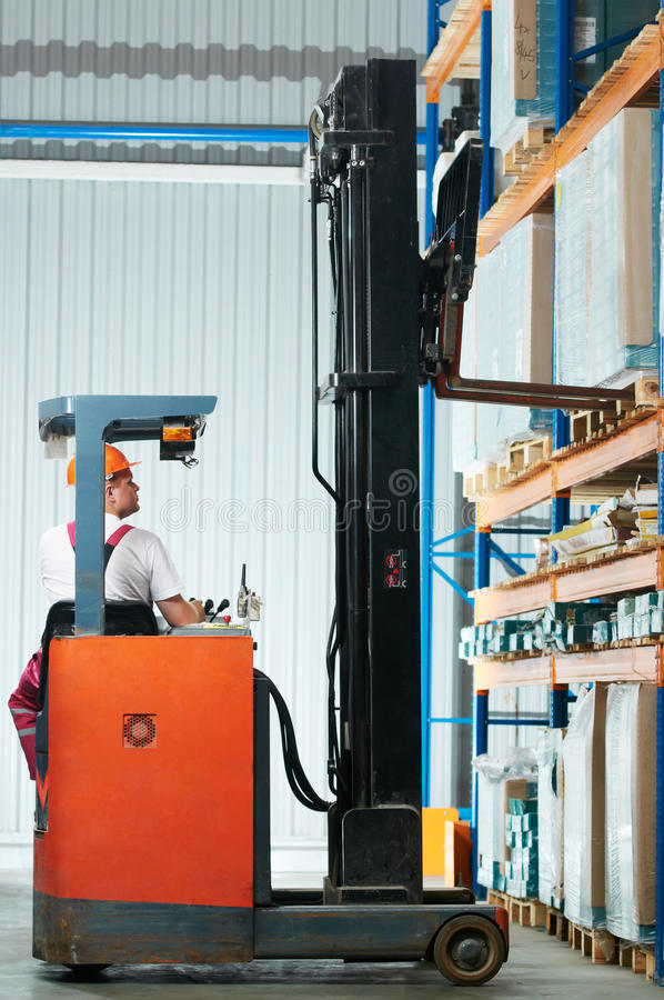 Warehouse forklift loader at work. Warehouse worker distributing goods in a storehouse with forklift truck loader stacker royalty free stock photo