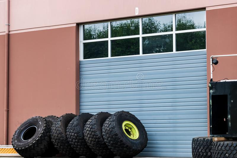 Warehouse industrial building windowed garage door with tires. Leaning in a row stock photography