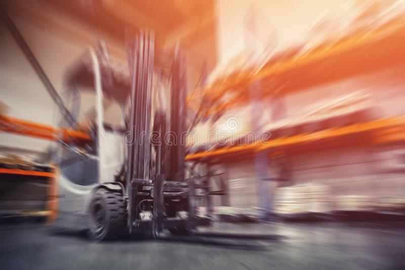 Warehouse industrial premises for storing materials and wood, forklift containers. Concept logistics, transport. Motion blur effect. Bright sunlight royalty free stock photo