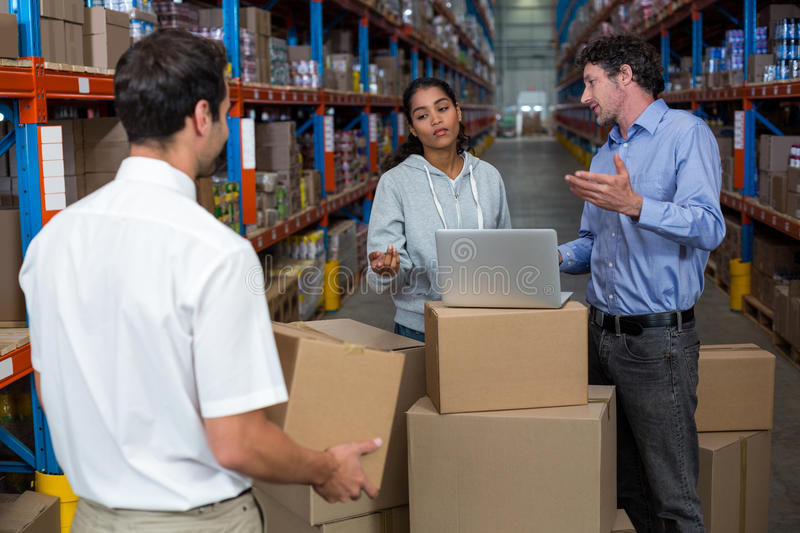 Warehouse manager carrying a box and his colleagues discussing. In the warehouse stock photo
