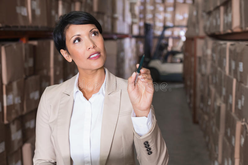 Warehouse manager checking her inventory. In a large warehouse royalty free stock image