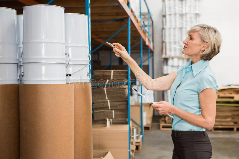 Warehouse manager checking her list on clipboard. In a large warehouse stock photo