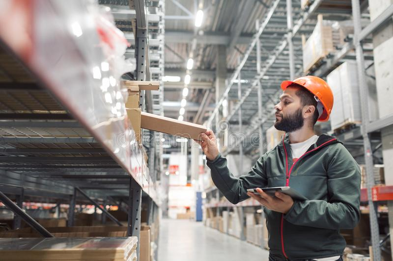 Warehouse manager checking his inventory in a large warehouse. Using the tablet via the Internet is checking stock availability royalty free stock image