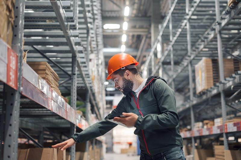 Warehouse manager checking his inventory in a large warehouse. Using the tablet via the Internet is checking stock availability stock images