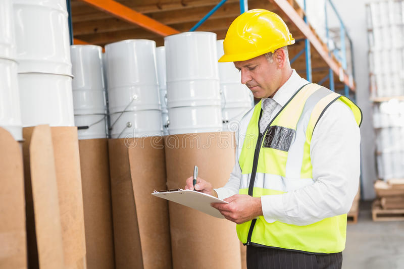 Warehouse manager checking his list on clipboard royalty free stock images