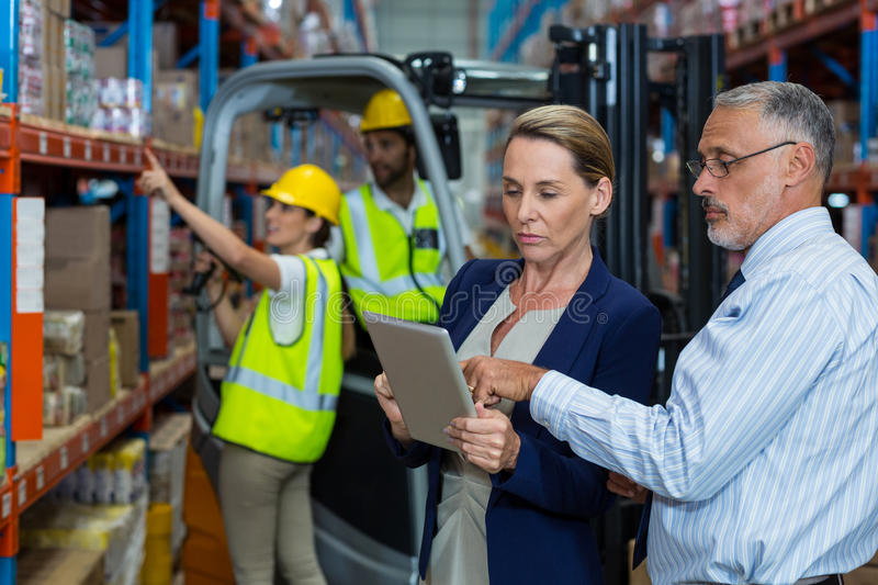 Warehouse manager and client discussing over digital tablet. In warehouse royalty free stock photos