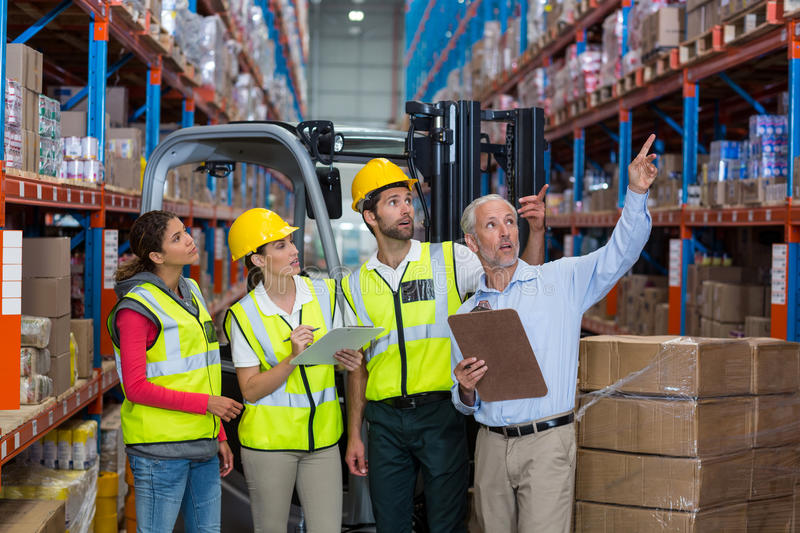 Warehouse manager and co-workers discussing over clipboard. In warehouse royalty free stock images