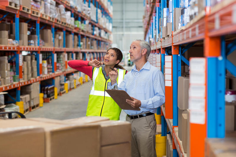 Warehouse manager and female worker interacting while checking inventory. In warehouse stock photo