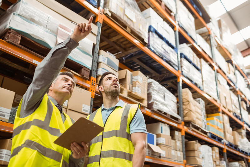 Warehouse manager and foreman working together. In a large warehouse royalty free stock image