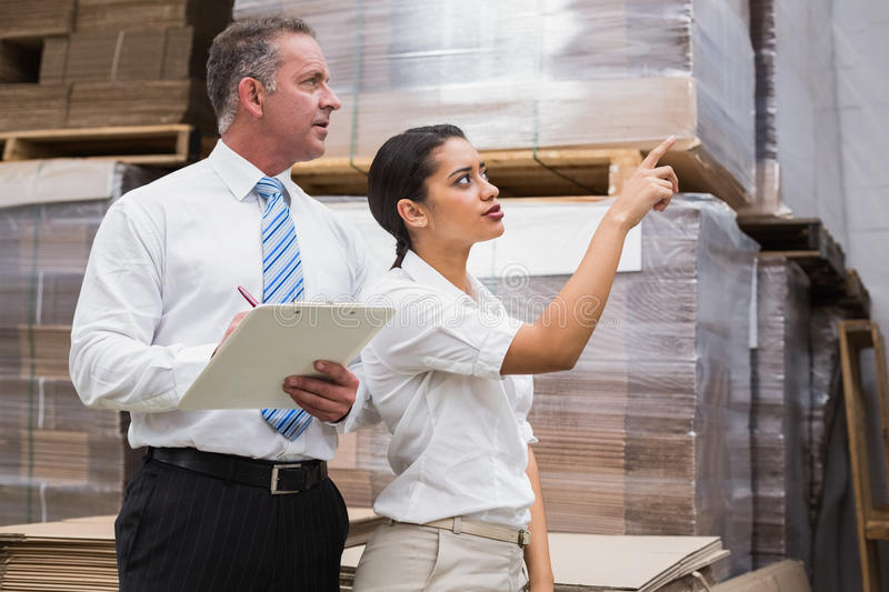 Warehouse manager and her boss checking inventory. In a large warehouse royalty free stock photos