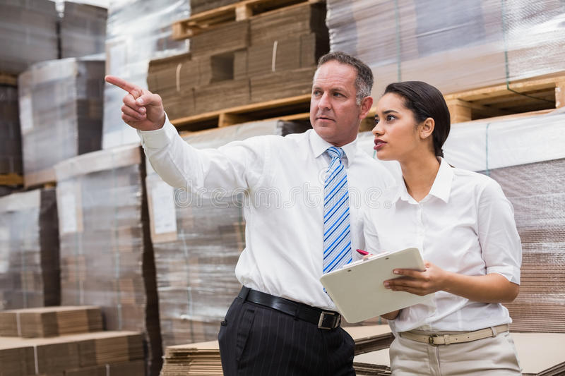 Warehouse manager and her boss checking inventory. In a large warehouse stock images