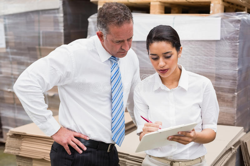 Warehouse manager and her boss working together. In a large warehouse stock photo