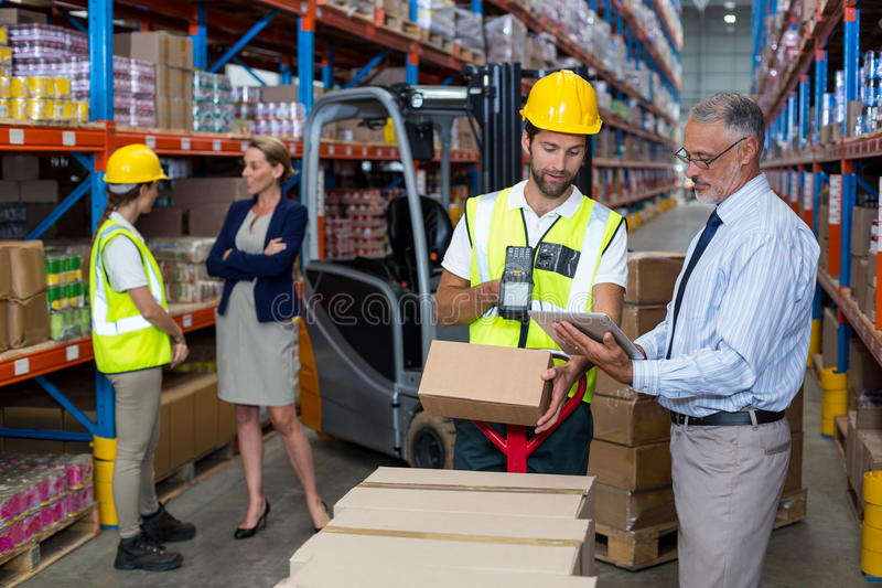 Warehouse manager holding digital tablet while male worker scanning barcode. In warehouse royalty free stock photo