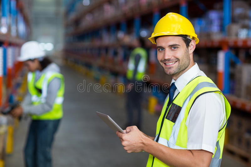 Warehouse manager holding digital tablet. Portrait of warehouse manager holding digital tablet in warehouse stock photography