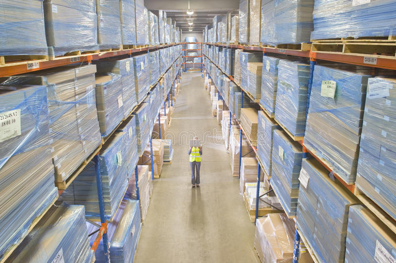 Warehouse manager holding laptop in aisle royalty free stock images