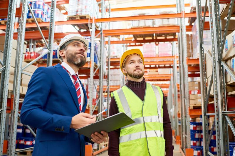 Warehouse Manager Instructing Worker. Waist up portrait of warehouse manager holding clipboard talking to worker wearing hardhat and reflective jacket while stock photo