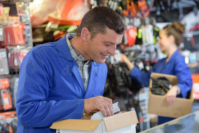 Warehouse manager looking in box in large warehouse stock photos