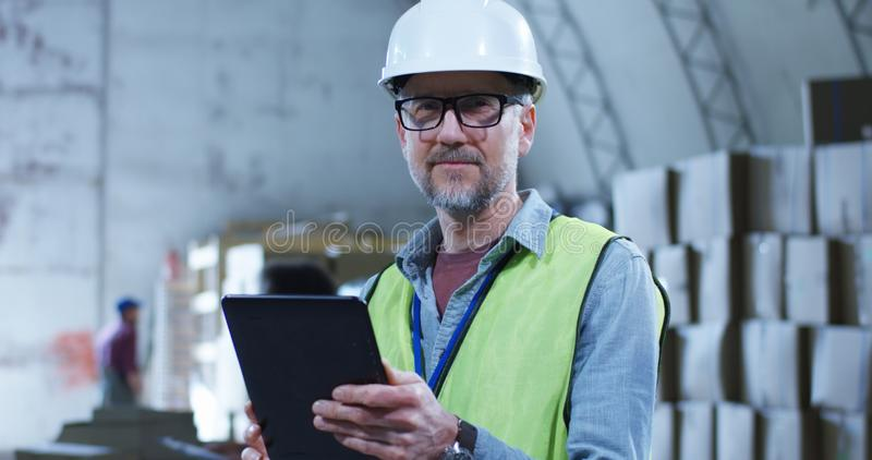 Warehouse manager looking at camera. Medium shot of warehouse manager looking at camera while staff in the background royalty free stock photography