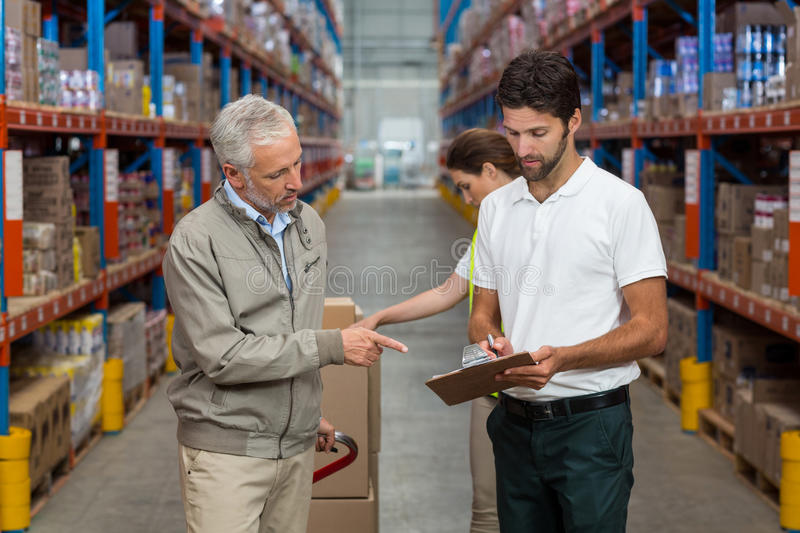 Warehouse manager and male worker interacting while working stock images