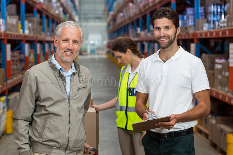 Warehouse manager and male worker smiling while working royalty free stock photo