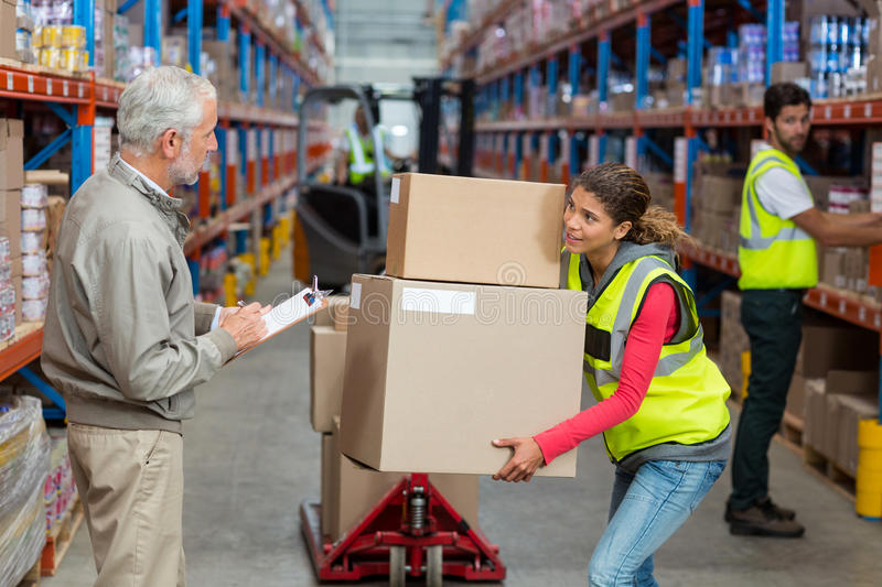 Warehouse manager noting on clipboard while female worker carrying cardboard boxes stock photo