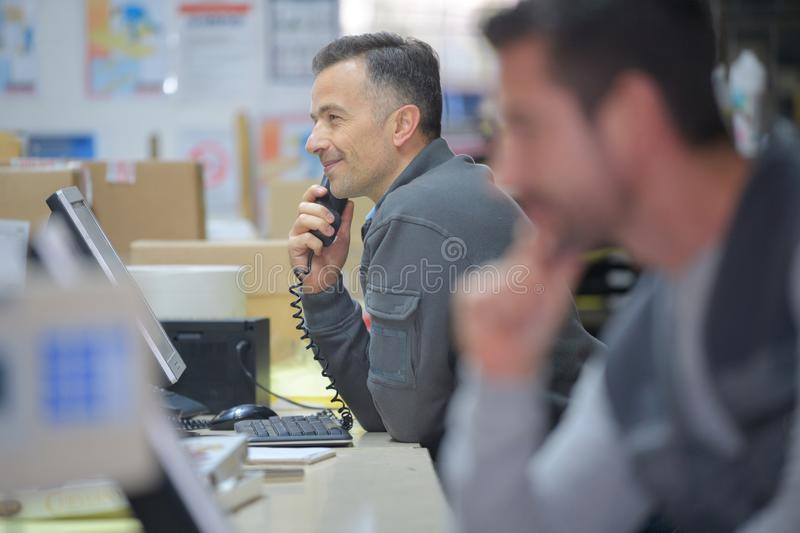 Warehouse manager on phone in warehouse. Warehouse manager on the phone in a warehouse royalty free stock images