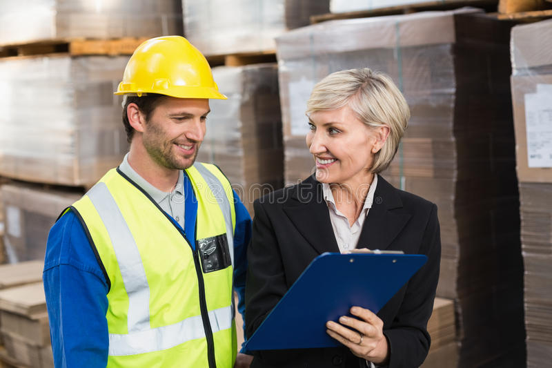 Warehouse manager showing clipboard to her colleague. In a large warehouse royalty free stock image