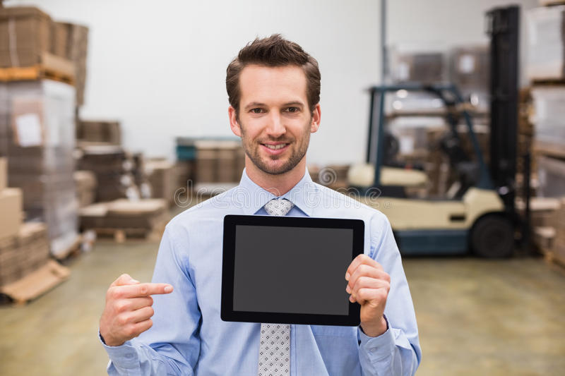 Warehouse manager showing tablet pc smiling at camera. In a large warehouse stock images