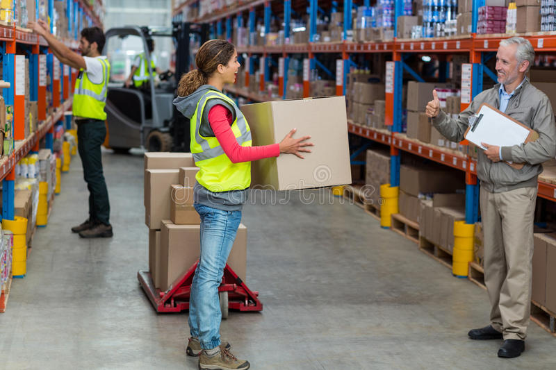 Warehouse manager showing thumbs up to female worker while carrying cardboard boxes royalty free stock images