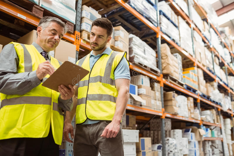 Warehouse manager speaking with foreman. In a large warehouse royalty free stock photos