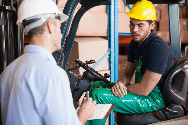 Warehouse manager talking with forklift driver. In warehouse royalty free stock images
