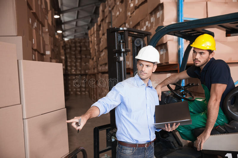 Warehouse manager talking with forklift driver. In warehouse stock photography