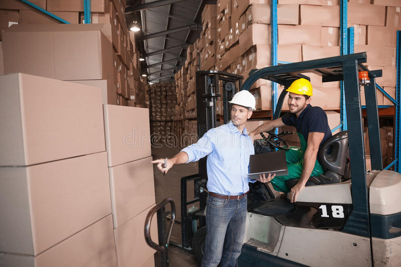 Warehouse manager talking with forklift driver. In warehouse royalty free stock photos