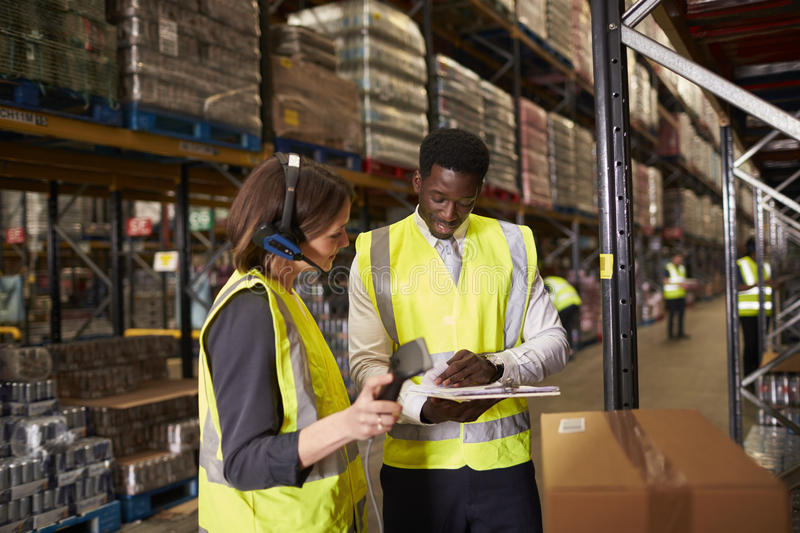 Warehouse manager talking with woman using barcode reader stock photography