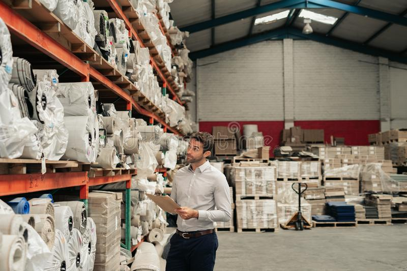 Warehouse manager using a clipboard while doing stock inventory stock photo