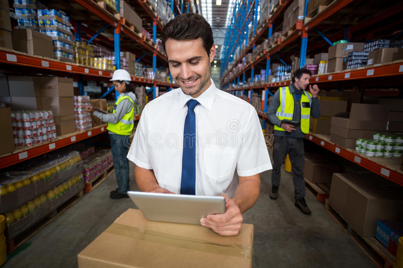 Warehouse manager using digital tablet. In warehouse royalty free stock image