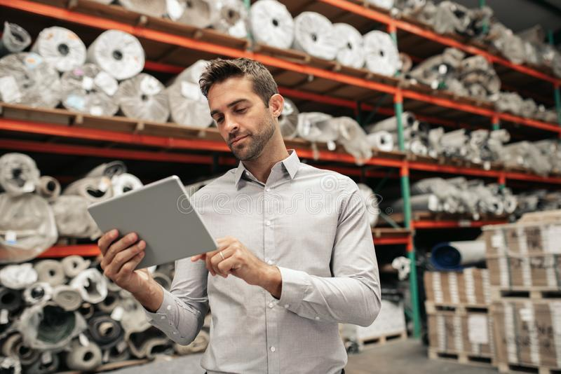 Warehouse manager using a digital tablet while tracing stock royalty free stock image