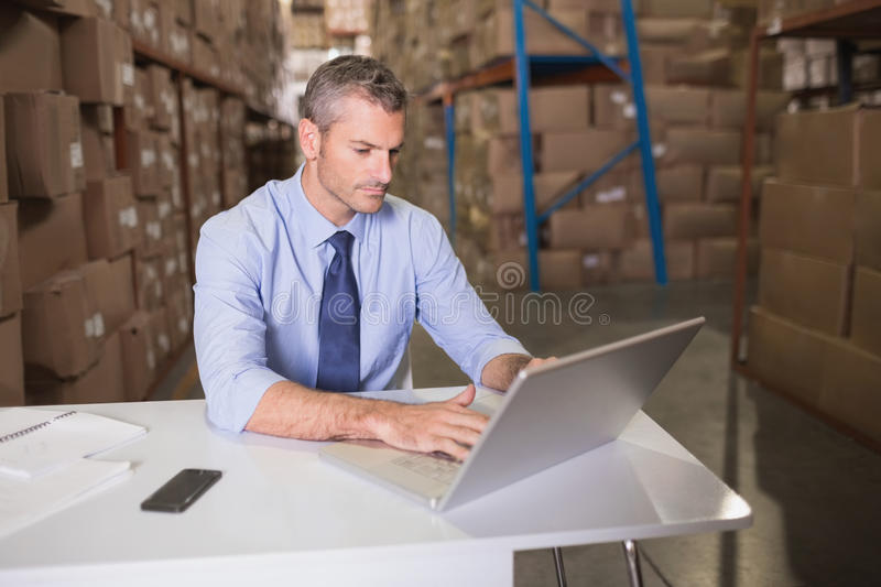 Warehouse manager using laptop. At desk royalty free stock photo