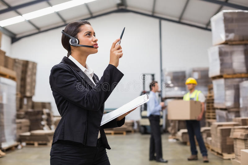 Warehouse manager wearing headset checking inventory. In a large warehouse stock images