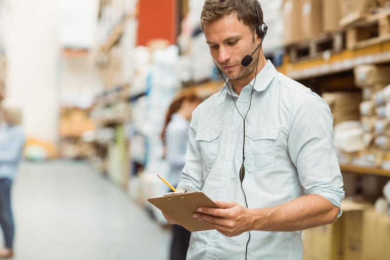Warehouse manager wearing headset writing on clipboard. In a large warehouse royalty free stock images