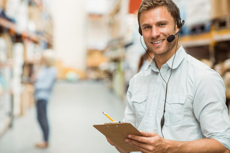 Warehouse manager wearing headset writing on clipboard. In a large warehouse royalty free stock photos