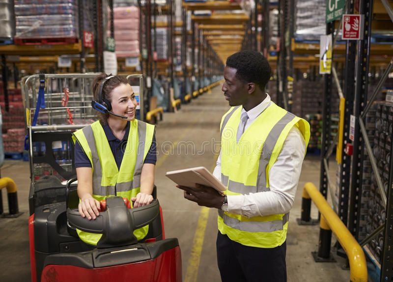 Warehouse manager and woman on tow tractor in discussion royalty free stock photos